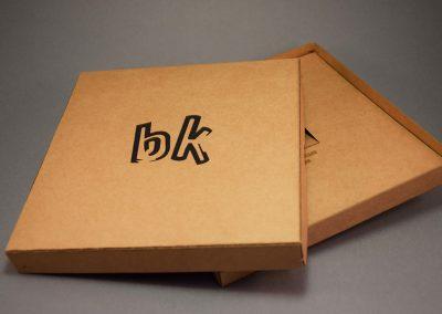Laserleikattu logo ja taustana musta kartonki